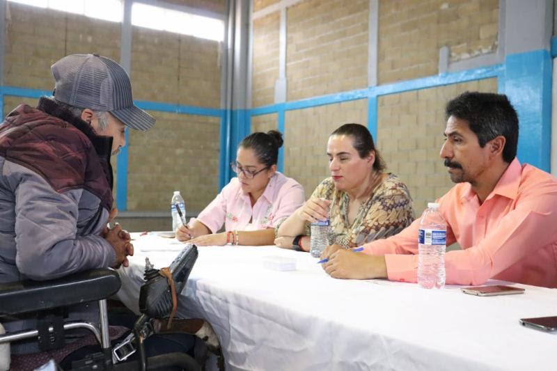 La directora del Instituto de Inclusión en Audiencia Pública atendiendo a una persona de la tercera edad en silla de ruedas en audiencia pública